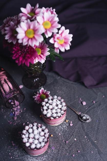 Una vista aérea del jarrón con un sabroso pastel de grosella negra sobre un fondo texturado negro Foto gratis