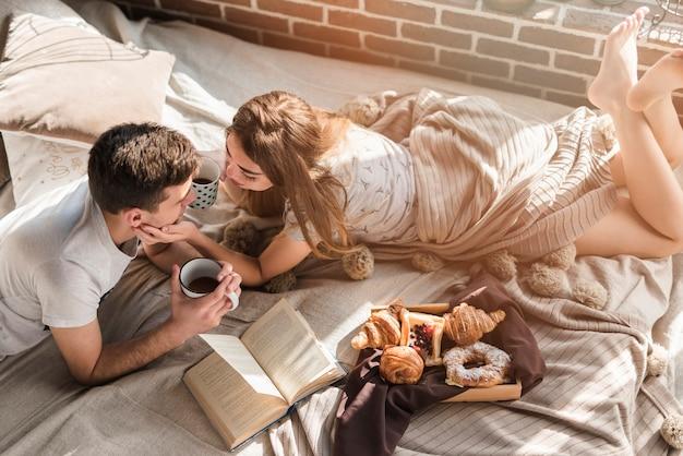 Una vista aérea de la joven pareja acostada en la cama desordenada con desayuno en la cama Foto gratis