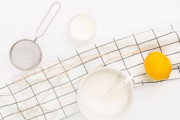 Vista aérea de limón; azúcar y utensilio de cocina. Foto gratis