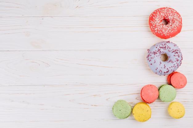 Una vista aérea de macarrones y donuts sobre fondo de textura de madera Foto gratis