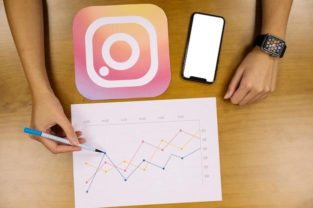 Vista aérea de mano analizando el gráfico de instagram Foto gratis
