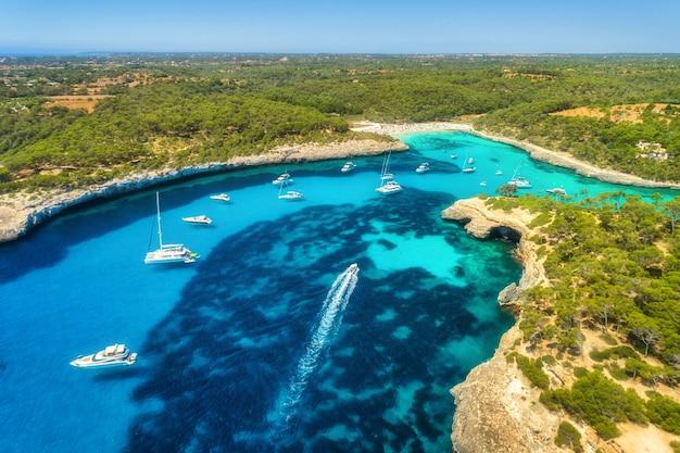 Vista aérea del mar transparente con agua azul, playa de arena, rocas, árboles verdes, yates y barcos en una mañana soleada en verano Foto Premium