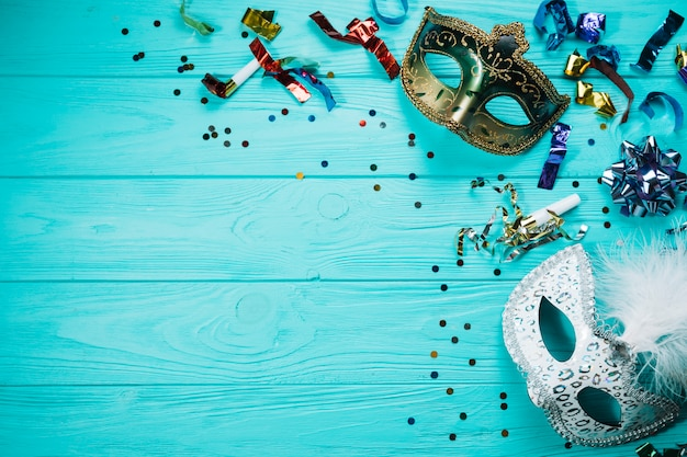 Vista aérea de una máscara de carnaval de plata y oro con decoraciones de fiesta en mesa de madera Foto gratis