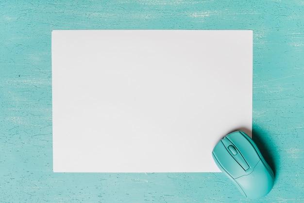 Vista aérea del mouse sobre papel blanco sobre fondo turquesa. Foto gratis