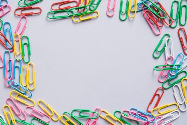 Vista aérea de muchos clips de papel coloridos formando marco Foto gratis