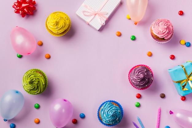 Una vista aérea de los muffins; globos gemas caja de regalo y velas sobre fondo rosa. Foto gratis