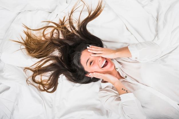Una vista aérea de una mujer joven sonriente que cubre su ojo con la mano acostada en la cama Foto gratis