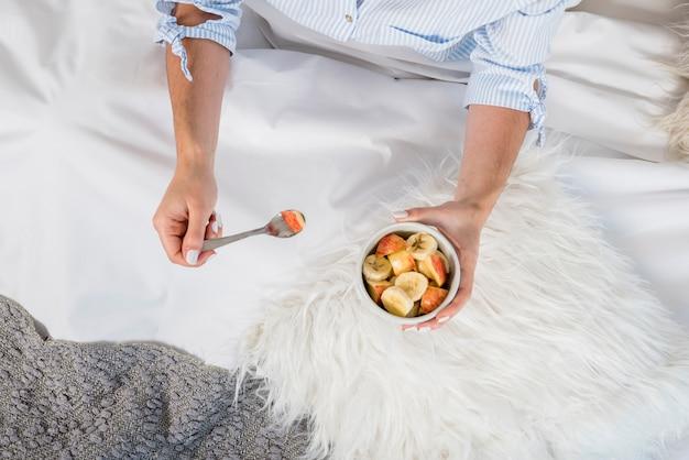 Una vista aérea de la mujer sentada en la cama con un tazón de ensalada de frutas Foto gratis