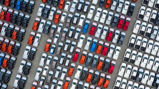 Vista aérea nueva terminal de exportación de automóviles, automóviles nuevos a la espera de importación y exportación en el puerto de aguas profundas. Foto Premium