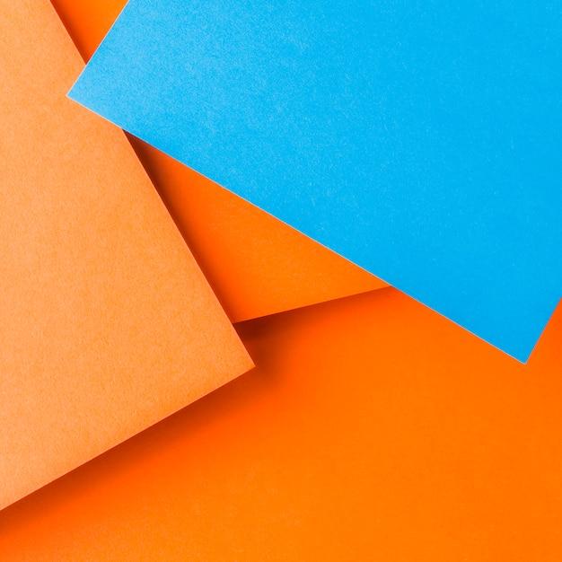 Una vista aérea de papel artesanal azul sobre el fondo liso de color naranja Foto gratis