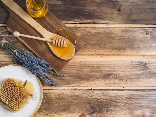 Una vista aérea de una pieza de panal de abeja; lavanda y miel en la mesa de madera Foto gratis