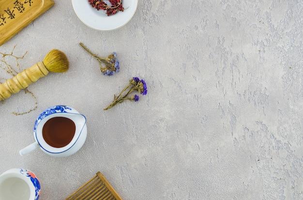 Una vista aérea de pincel con té de hierbas sobre fondo de textura concreta Foto gratis