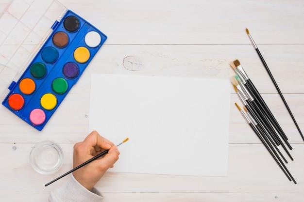 Vista aérea de la pintura de la mano humana en papel blanco en blanco con pincel Foto gratis