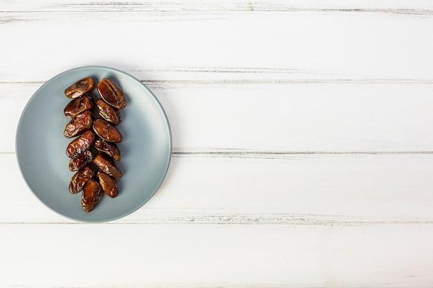 Una vista aérea de la placa gris con fechas jugosas dispuestas en el escritorio de madera blanco Foto gratis