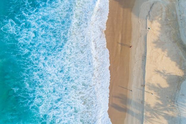 Vista aérea playa de arena y olas hermoso mar tropical en la mañana imagen de temporada de verano por vista aérea drone shot, vista de ángulo alto de arriba hacia abajo. Foto Premium