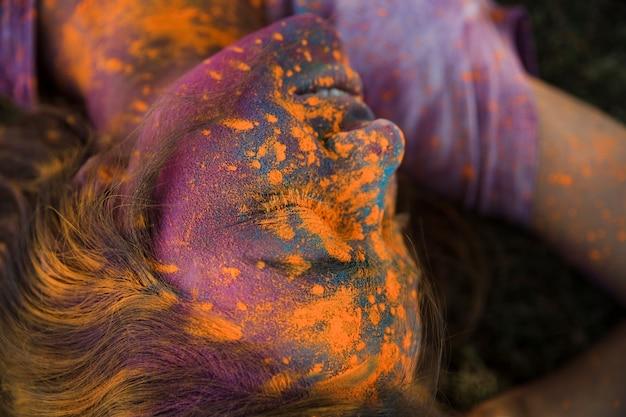 Vista aérea del polvo de color naranja holi en la cara de la mujer. Foto gratis