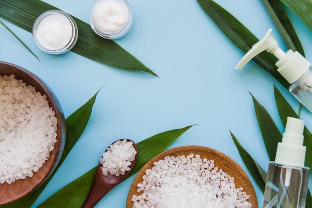 Una vista aérea de un producto de cosmética natural de cuidado corporal sobre fondo azul Foto gratis
