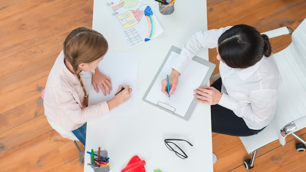 Una vista aérea de un psicólogo femenino tomando nota con la niña dibujando en papel Foto gratis