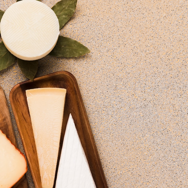 Vista aérea de queso blanco; queso parmesano y queso manchego español dispuestos sobre un fondo liso Foto gratis