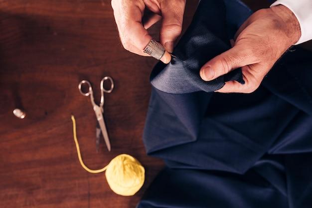 Vista aérea de la tela de costura de una mano de un hombre con aguja. Foto gratis