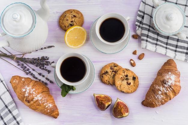 Vista aérea de la tetera; galletas; café; cuerno; higo; y limón en la mesa Foto gratis