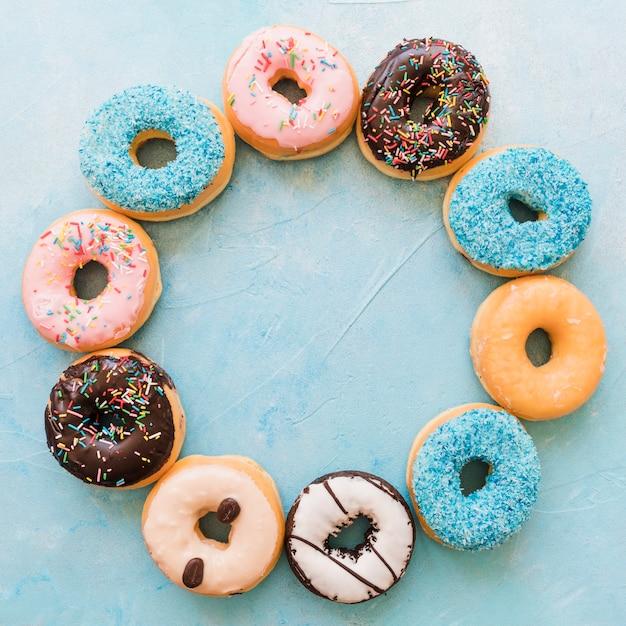 Vista aérea de varias rosquillas frescas que forman un marco circular. Foto gratis
