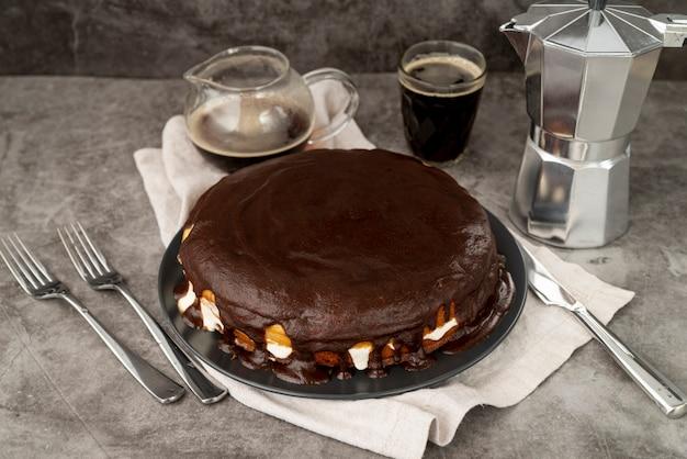 Vista alta pastel de chocolate con café recién hecho Foto gratis