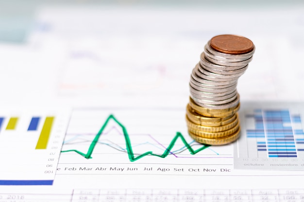 Vista alta pila de monedas en diagramas estadísticos Foto gratis