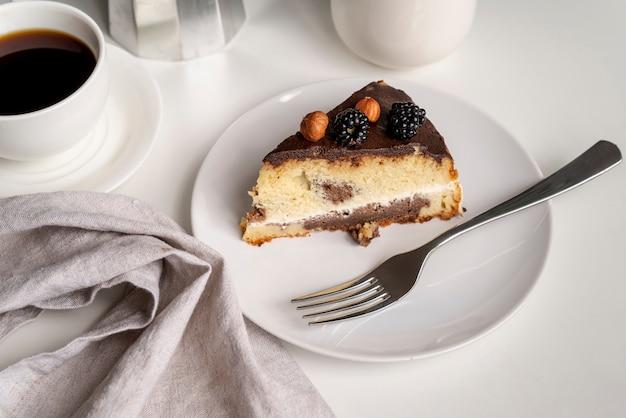 Vista alta rebanada de pastel con café Foto gratis