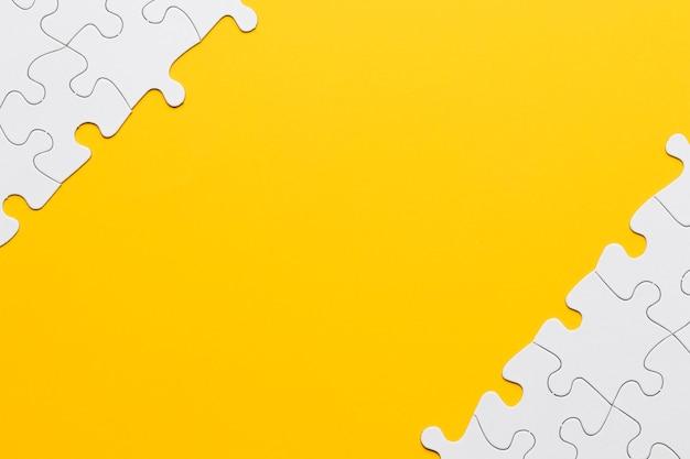 Vista de alto ángulo de pieza de rompecabezas blanco en superficie amarilla Foto gratis
