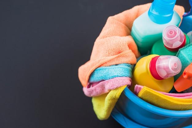 Vista de alto ángulo de productos de limpieza en la cesta sobre fondo negro Foto gratis