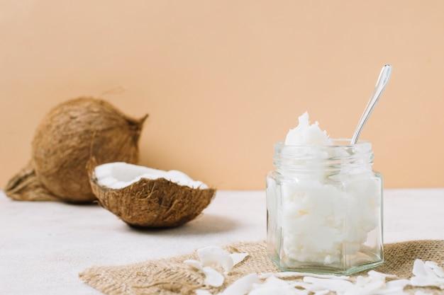 Vista de ángulo bajo aceite de coco en frasco con nuez Foto gratis