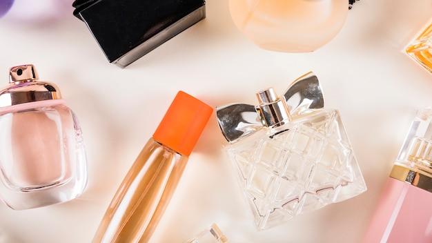 Vista de ángulo alto de botellas de perfume sobre fondo blanco Foto gratis