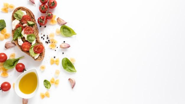 Vista de ángulo alto de bruschetta con pasta cruda farfalle; diente de ajo; tomate; petróleo; hoja de albahaca contra aislados sobre fondo blanco Foto gratis