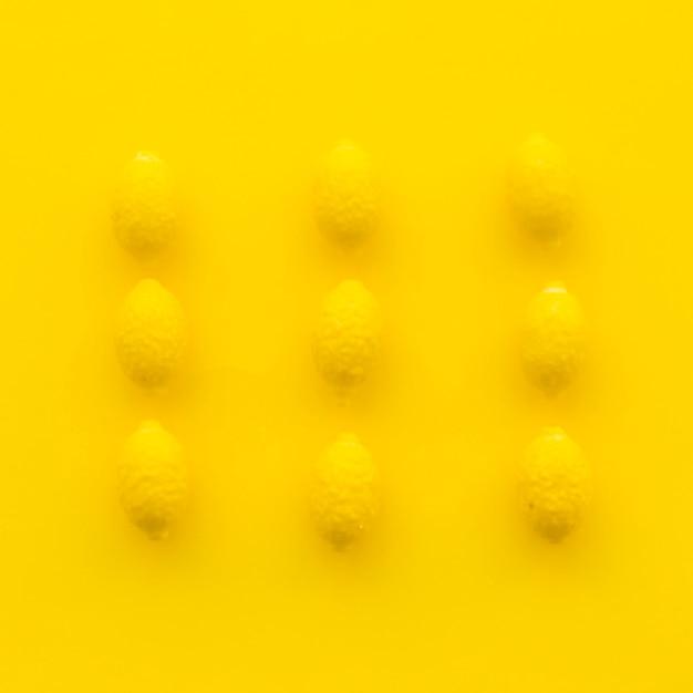 Vista de ángulo alto de caramelos de limón sobre superficie amarilla Foto gratis