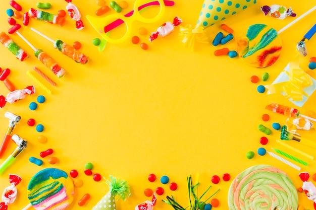 Vista de ángulo alto de caramelos; piruletas; velas; fiesta en y soplador en superficie amarilla Foto gratis
