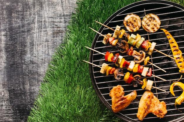 Vista de ángulo alto de carnes y vegetales a la parrilla en parrilla Foto gratis