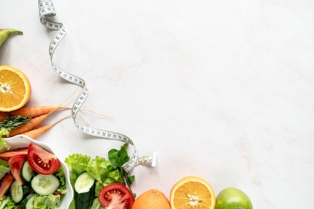 Vista de ángulo alto de la cinta métrica cerca de verduras y frutas orgánicas sobre fondo blanco Foto gratis