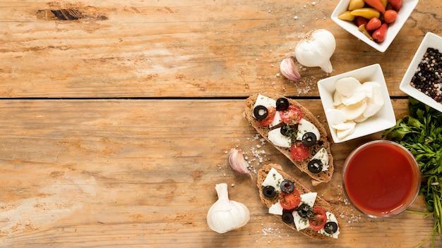 Vista de ángulo alto de comida italiana con ingredientes sobre mesa de madera Foto gratis