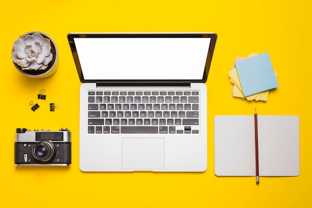 Vista de ángulo alto de la computadora portátil; cámara; stationeries y planta suculenta en superficie amarilla Foto gratis