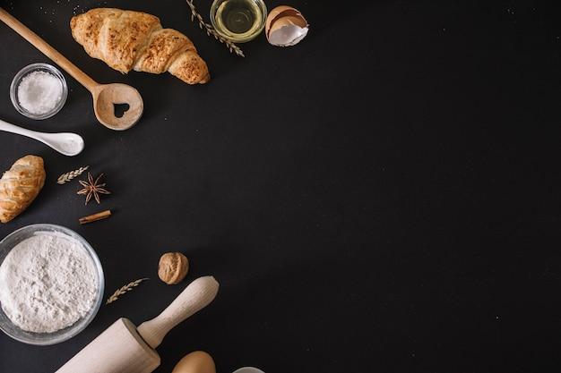 Vista de ángulo alto de croissants; ingredientes para hornear y utensilios en superficie negra Foto gratis