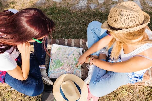 Vista de ángulo alto de dos excursionistas que buscan dirección en el mapa Foto gratis