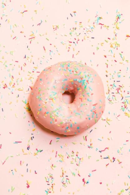 Vista de ángulo alto de dulce donut rodeado de colorido asperja Foto gratis