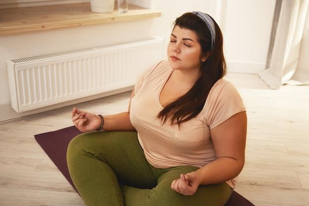 Vista de ángulo alto de elegante joven gordita con sobrepeso vestida con leggings y camiseta meditando con las piernas cruzadas, cerrando los ojos, tomados de la mano en mudra, practicando técnicas de respiración Foto gratis