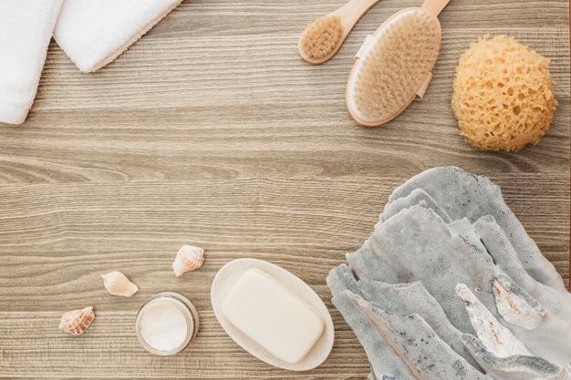 Vista de ángulo alto de esponja; concha; jabón; cepillo; toalla y crema hidratante sobre fondo de madera. Foto gratis