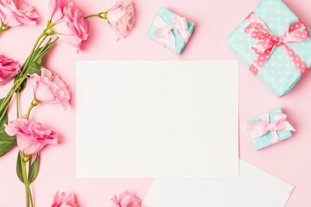 Vista de ángulo alto de flor rosa; papel blanco blanco y caja de regalo decorativa. Foto gratis