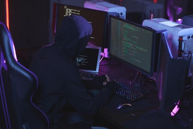 Vista de ángulo alto en hacker de seguridad cibernética irreconocible con capucha mientras trabaja en código de programación en una habitación oscura, espacio de copia Foto Premium