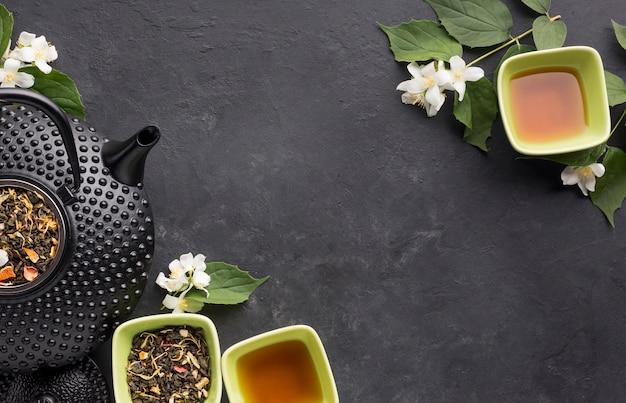 Vista de ángulo alto de hojas secas y té de hierbas sobre fondo texturizado Foto gratis