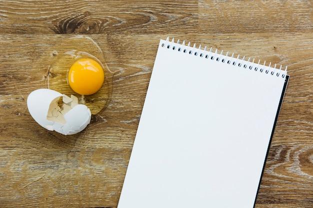 Vista de ángulo alto de la libreta de espiral y el huevo en el escritorio de madera Foto gratis