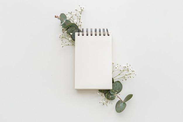 Vista de ángulo alto de la libreta de espiral vacía con hojas y flores de aliento de bebé en superficie blanca Foto gratis